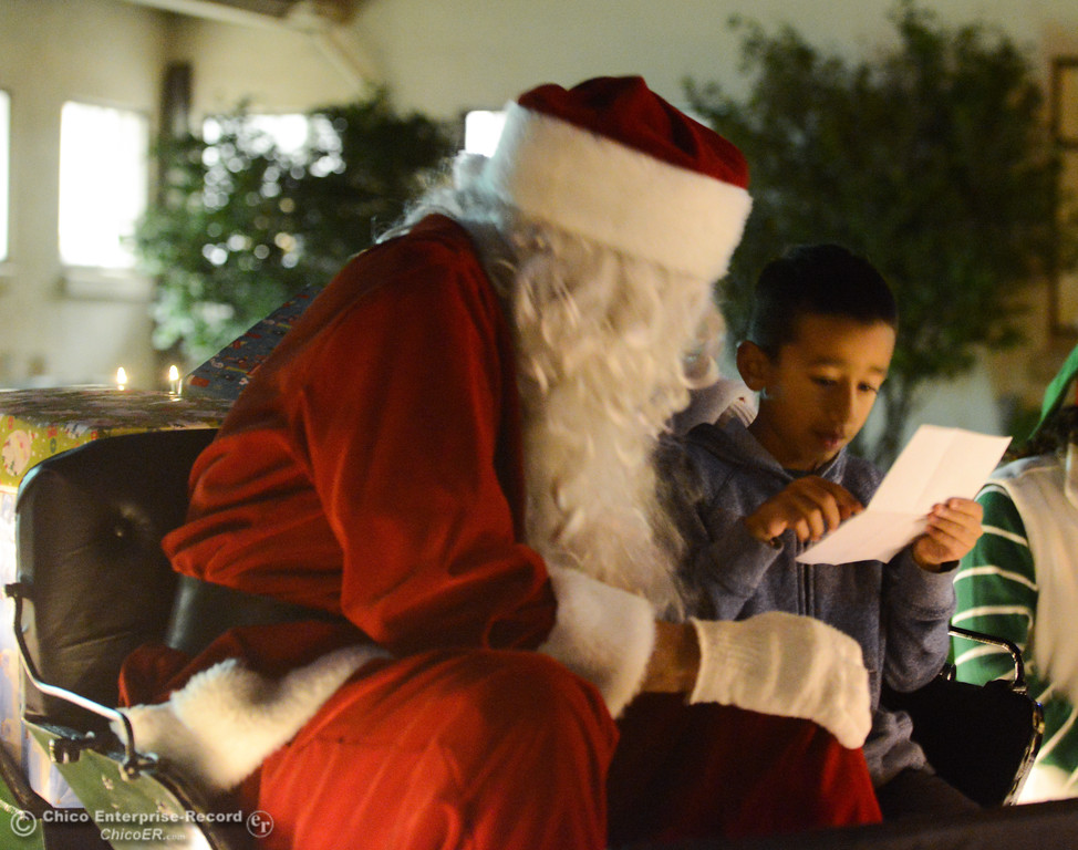 . Jayson Kuhne, 7, reads his Christmas wish list to Santa Claus during Enloe\'s annual tree lighting ceremony Tuesday November 28, 2017 in Chico, California. (Emily Bertolino -- Enterprise-Record)