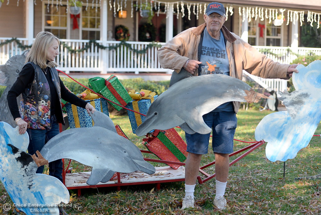 . Doug and Michele Wurlitzer hold up broken dolphin decorations in their front yard Tuesday.  Doug and Michele Wurlitzer always decorate their yard for Christmas and have been on the Tour of Lights for years. This year they have experienced vandalism including a four wheeler running through their yard. Tues. Nov. 28, 2017. (Bill Husa -- Enterprise-Record)