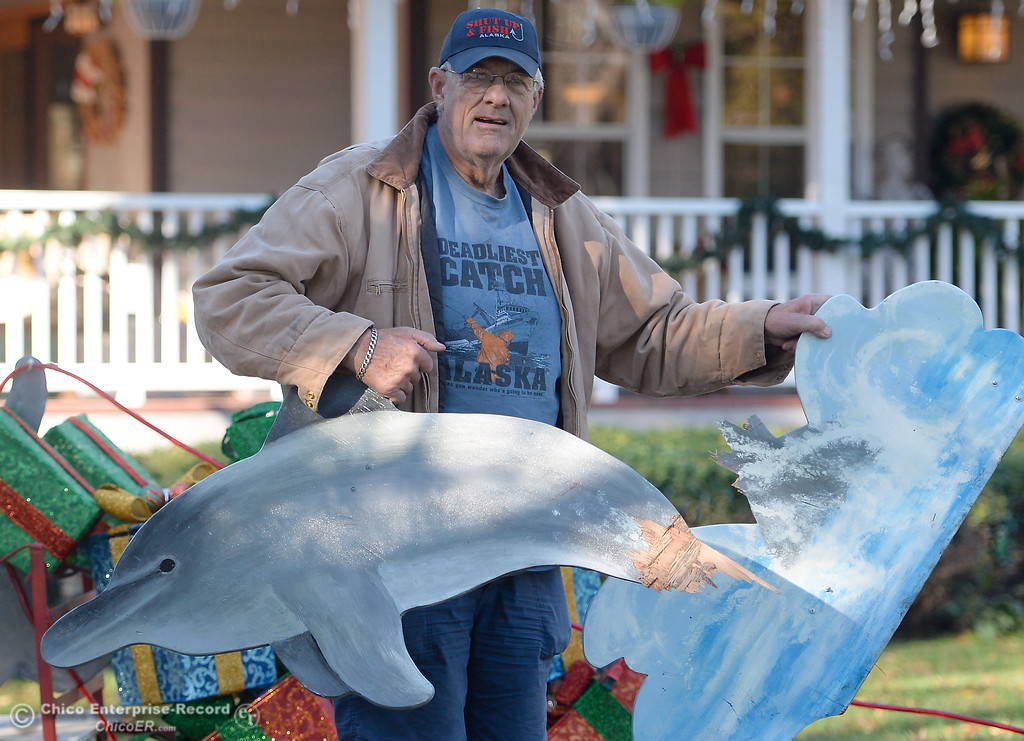 . Doug Wurlitzer holds up a broken dolphin decoration in his front yard Tuesday. Doug and Michele Wurlitzer always decorate their yard for Christmas and have been on the Tour of Lights for years. This year they have experienced vandalism including a four wheeler running through their yard. Tues. Nov. 28, 2017. (Bill Husa -- Enterprise-Record)