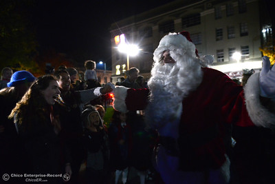 Santa Claus greets fans of all ages as he arrives at Chico's Christmas tree lighting. The 95-foot redwood tree behind the City Plaza stage lights up Friday, Dec. 2, 2016 in Chico, California. For the past three years, the tree has been decorated by M&S Wesley Tree Service, which has donated staff time and equipment to keep the annually awaited community event going, but this year the city's Public Works Department took over decorating duties. Before the lighting ceremony, the Sounds of the Valley Women's Chorus and Children's Choir of Chico sang Christmas carols and Santa Claus arrived on a vintage fire engine. (Dan Reidel -- Enterprise-Record)