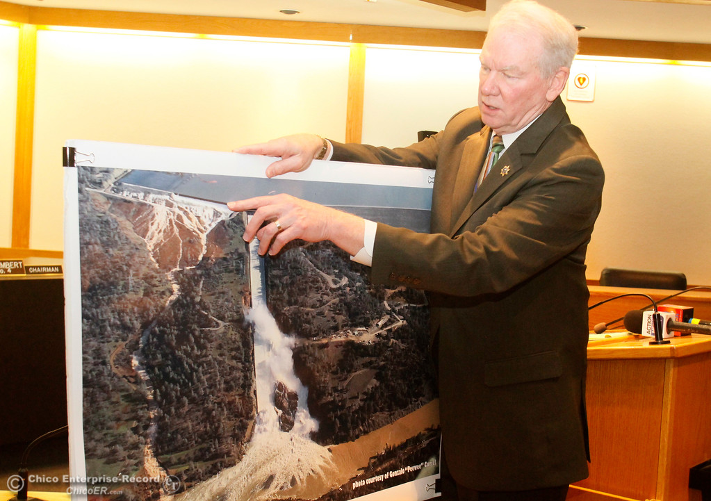 ". Butte County District Attorney Mike Ramsey uses a photo taken by pilot Gonzalo ""Peewee\"" Curiel as water was pouring over the emergency spillway last February as he discusses the lawsuit his office is bringing against the California Department of Water Resources during a press conference Wednesday, Feb. 7, 2018, in Oroville, California. (Dan Reidel -- Enterprise-Record)"