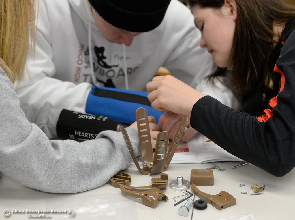 . Left to right, Tierra Friemoth, Flynn Davis and Taylor Hensley assemble an articulated hand using only one hand each Wednesday Feb. 14, 2018. The students were building them using only one hand to give them some perspective on the project.  (Bill Husa -- Enterprise-Record)