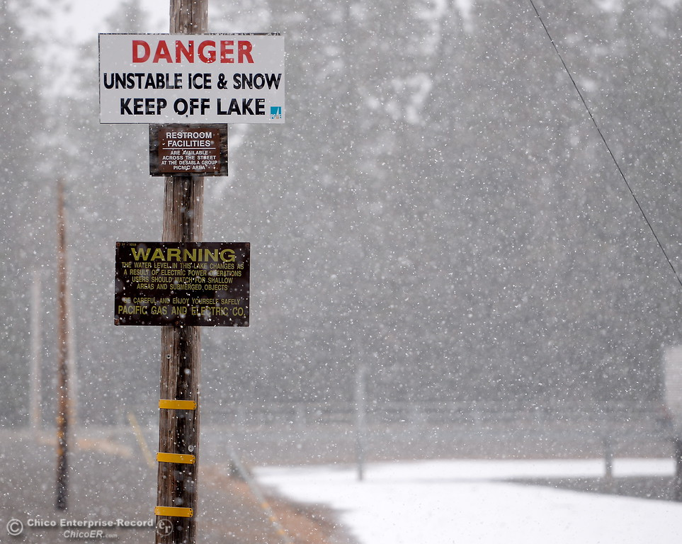 . A sign warns of unstable ice and snow as snow flurries are seen at the partially frozen DeSabla Reservoir Thurs. Feb. 22, 2018.  (Bill Husa -- Enterprise-Record)
