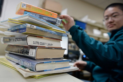 Library Assistant, extra help employee Alex Chen slides books over an RFID reader at the Chico library Thurs. Feb. 2, 2017. (Bill Husa -- Enterprise-Record)