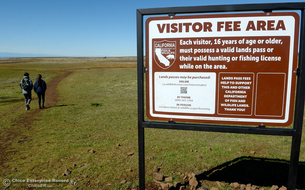 . Cliff Chao left and Holly Shafer of Davis walk past the visitor fee sign as they head out on a stroll through the wildflowers just beginning to bloom on Table Mountain Monday March 5, 2018. Hikers 16-years or older are now required to have a Lands Pass or valid hunting or fishing license. (Bill Husa -- Enterprise-Record)