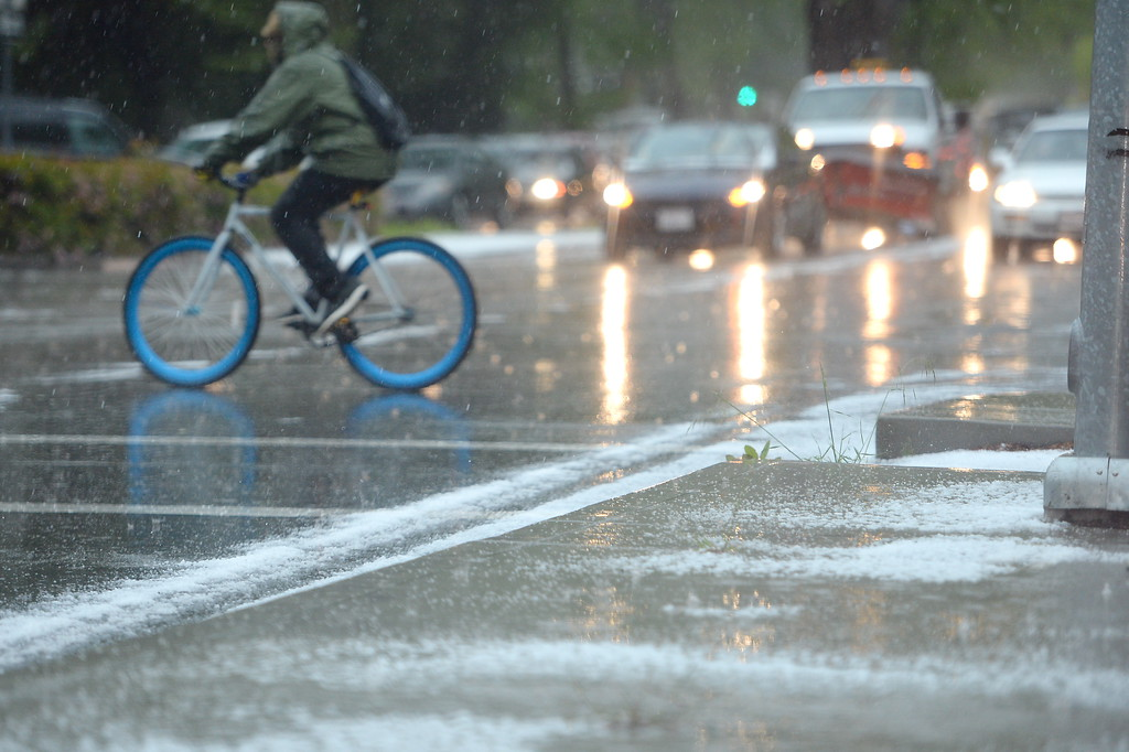 . A bicyclist makes their way through a hailstorm along the Esplanade during a thunderstorm in Chico, Calif. Thurs. April 13, 2017. (Bill Husa -- Enterprise-Record)