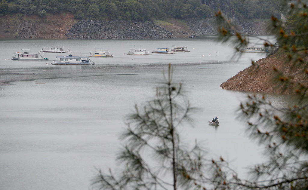 . A pair of hearty Lake Oroville fishermen don\'t seem to mind the rainy weather Tuesday as they cast a line near houseboats moored at the Forever Resorts Limesaddle Marina Tuesday April 11, 2017. (Bill Husa -- Enterprise-Record)