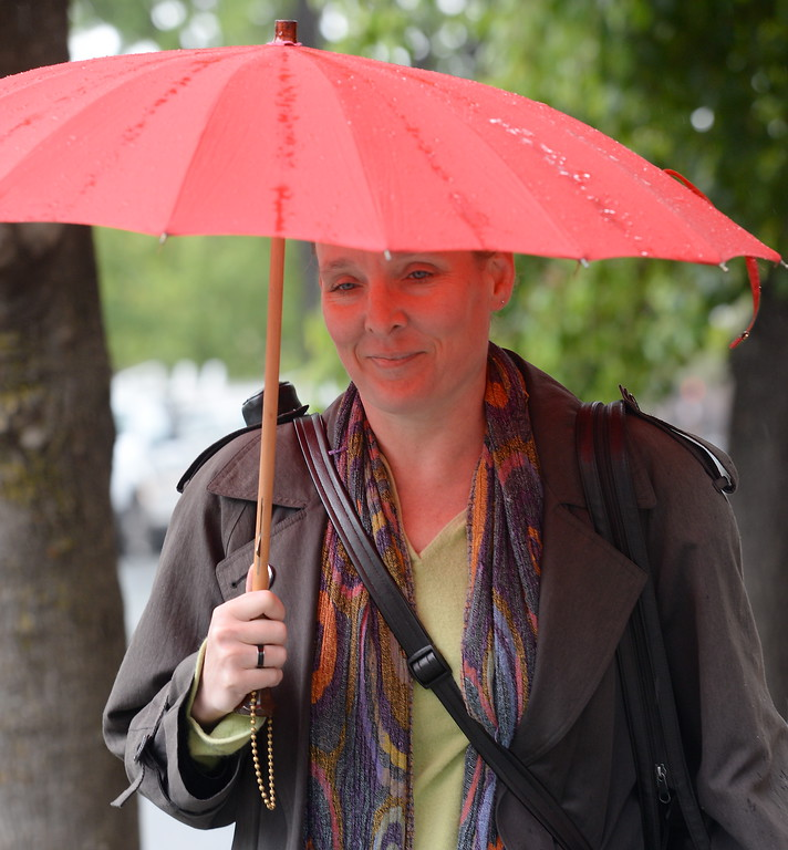 . Cathy Wagner of Chico walks along 4th Street with her red umbrella as the rain comes down in Chico, Calif. Monday April 16, 2018. (Bill Husa -- Enterprise-Record)