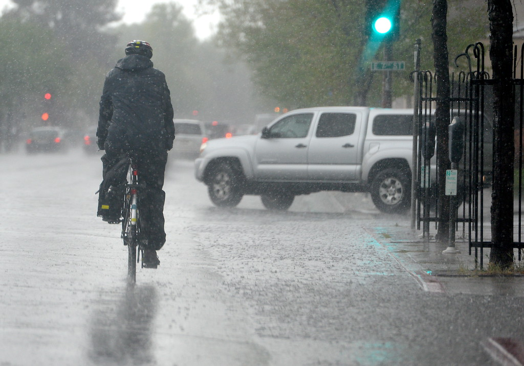 . A bicycclist braves heavy rain and hail as he makes his way down Main Street in Chico as a big black cloud unleashes it\'s power over Chico, Calif. Monday April 16, 2018. (Bill Husa -- Enterprise-Record)