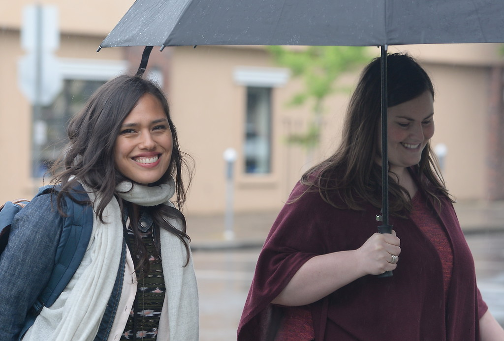 . Aidee Orejel at left smiles as she and Sarah Sullivan share an umbrella as the rain comes down in Chico, Calif. Monday April 16, 2018. (Bill Husa -- Enterprise-Record)