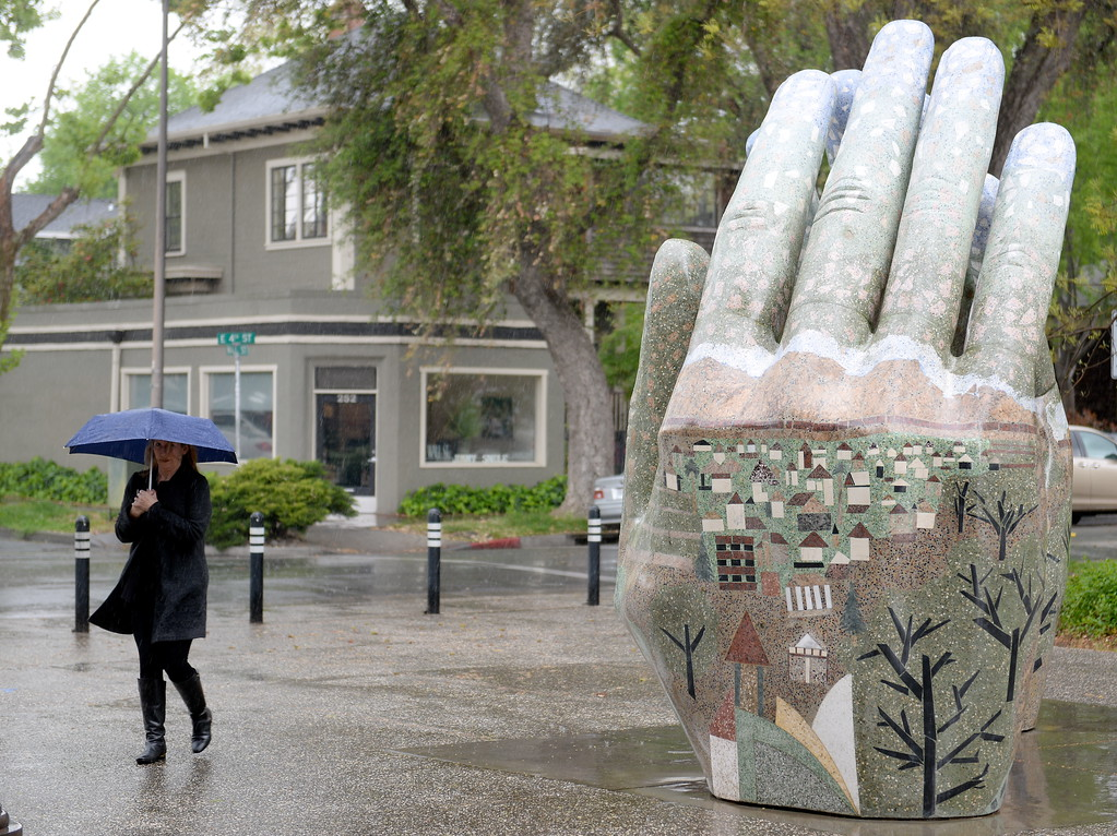 . Debbie Collins walks past the recently refurbished hands artwork near the Chico Municipal Center as the rain comes down in Chico, Calif. Monday April 16, 2018. (Bill Husa -- Enterprise-Record)
