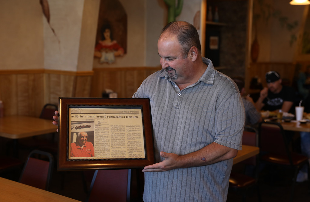 . La Comida Mexican Restaurant turns 50 this year. Owner Michael Pavis Jr. looks down at a newspaper article about his father, Michael Pavis Sr., from 1994, April 19, 2018, in Chico, California. (Carin Dorghalli -- Enterprise-Record)