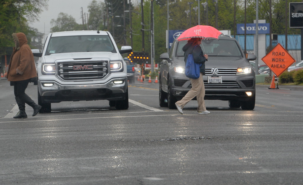 . Pedestrians make their way across Cohasset Road at the East Ave intersection as the rain comes down in Chico, Calif. Monday April 16, 2018. (Bill Husa -- Enterprise-Record)