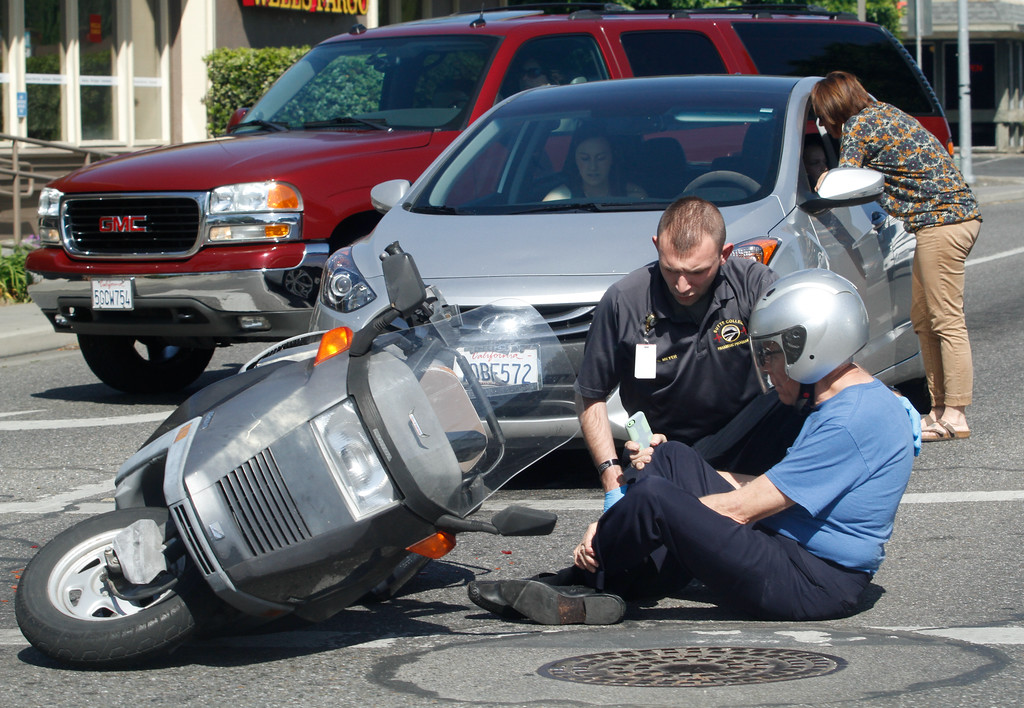 . A medical technician helps a scooter rider who appears to have fallen Wednesday, April 25, 2018, at the corner of East Avenue and Cohasset in Chico, California. (Dan Reidel -- Enterprise-Record)