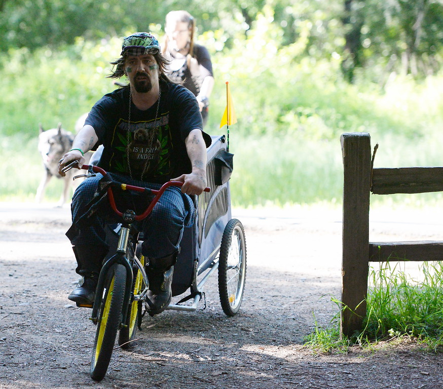 . A man on a small bicycle tows a baby trailer with loud music playing from it in Bidwell Park in Chico, Calif. Monday April 23, 2018. (Bill Husa -- Enterprise-Record)