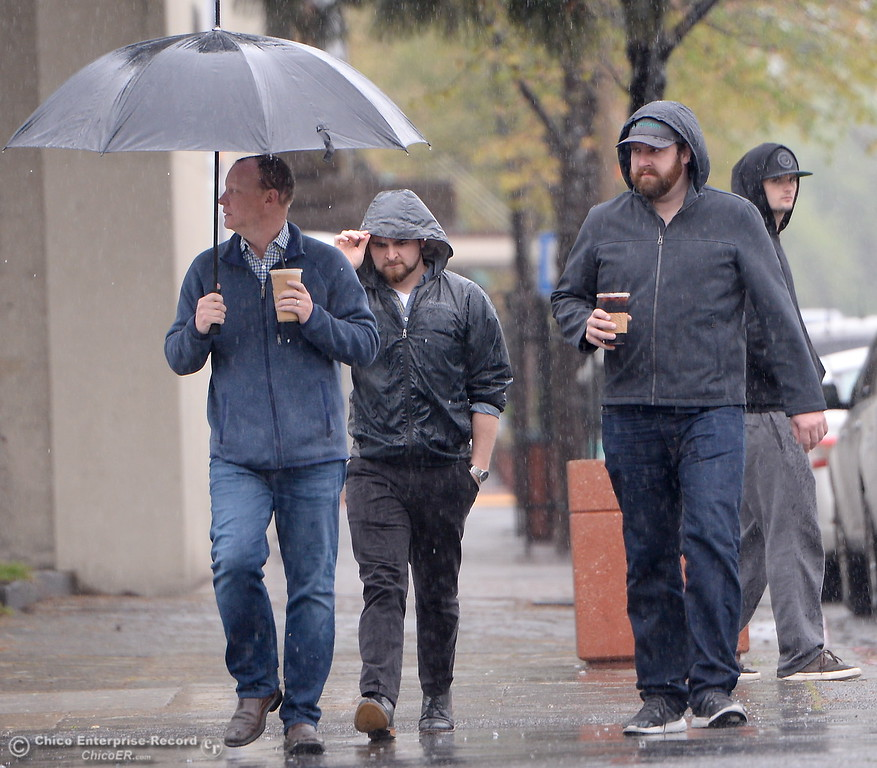 . People hunker beneath umbrellas as they make their way through the rain in downtown Chico, Calif. Friday, April 6, 2018. (Bill Husa -- Enterprise-Record)