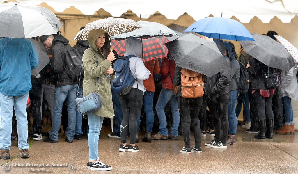 . People hunker beneath umbrellas during the CSUC Great Debate at City Plaza in downtown Chico, Calif. Friday, April 6, 2018. (Bill Husa -- Enterprise-Record)