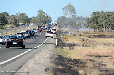Traffic slows to one lane while firefighters mop up a series of spot fires that started along Skyway above Chico, Calif. Thursday May 10, 2018.  (Bill Husa -- Enterprise-Record)