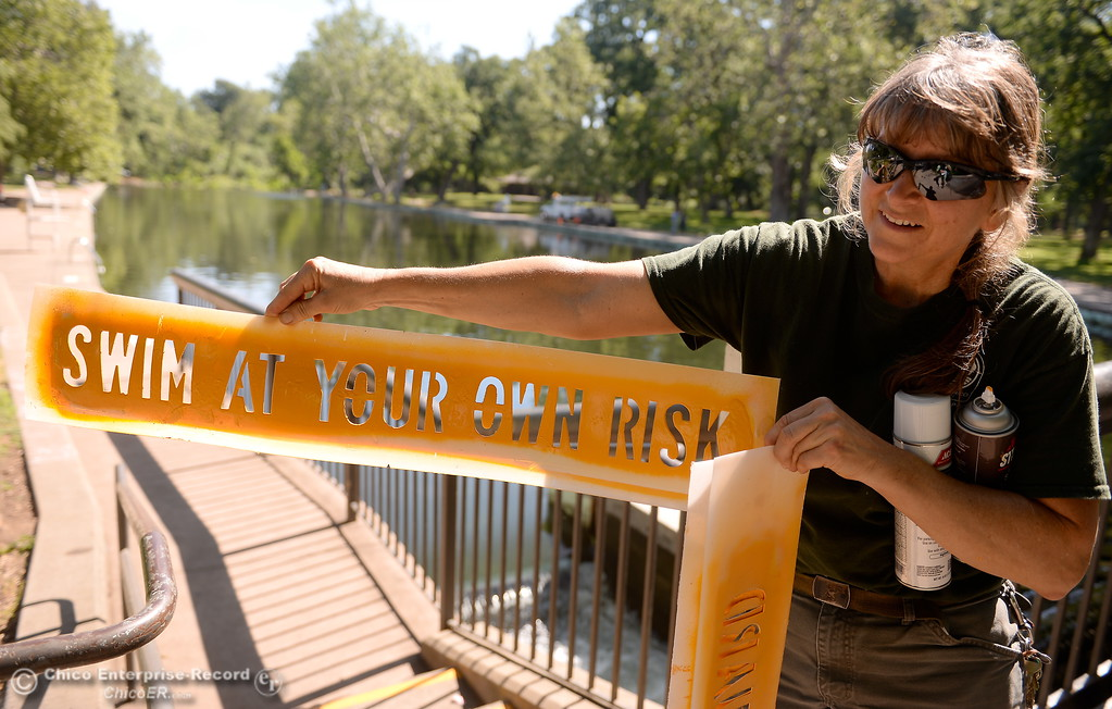 . City of Chico Maintenance worker Peggy Henry shows the stencil of a sign she has been painting around Sycamore Pool at the One Mile Recreation Area in Bidwell Park Tuesday.   Sycamore Pool at the One Mile Recreation Area in Bidwell Park will delay their opening this year due to high water. Signs are on display warning swimmers to swim at their own risk when no lifeguard is on duty and also to note that debris piled up on the bottom of the pool makes the deep end much shallower so no diving is permitted Tues. May 23, 2017. (Bill Husa -- Enterprise-Record)