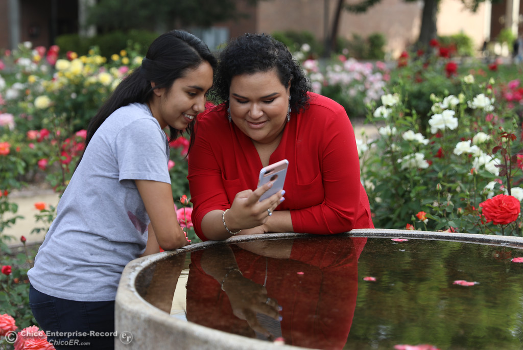 . Melissa Chavez and Gisele Vivas look at pictures they\'ve taken in the Rose Garden, May3, 2018,  in Chico, California. (Carin Dorghalli -- Enterprise-Record)