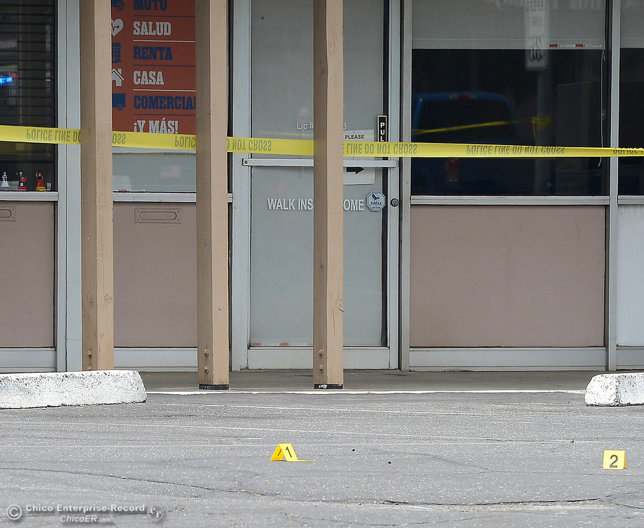 . Evidence markers are seen in the parking lot at Cost-U-Less Insurance as police investigate a shooting Wednesday, June 7, 2017, that began at Cohasset and the Esplanade and involved chases in several directions in Chico, California. (Dan Reidel -- Enterprise-Record)