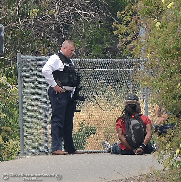 . Chico police Detective Peter Durfee, left, talks to a man officers detained on the bike path Wednesday, June 7, 2017, at The Esplanade and Lindo Channel as police investigate a shooting Wednesday, June 7, 2017, that began at Cohasset and the Esplanade and involved chases in several directions in Chico, California. (Dan Reidel -- Enterprise-Record)