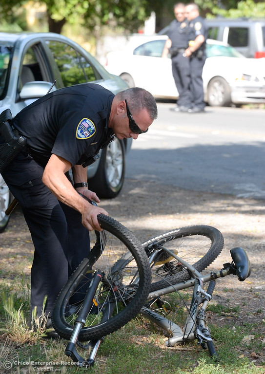 . Chico Police Officer Greg Rogers looks at a bike after a man was injured in a vehicle vs bicycle hit and run near the intersection of Humboldt Ave. and Olive St. in Chico, Calif. Monday June 5, 2017. The driver of the white BMW fled the scene by jumping into a black pickup, the bicycle rider was transported to Enloe. (Bill Husa -- Enterprise-Record)
