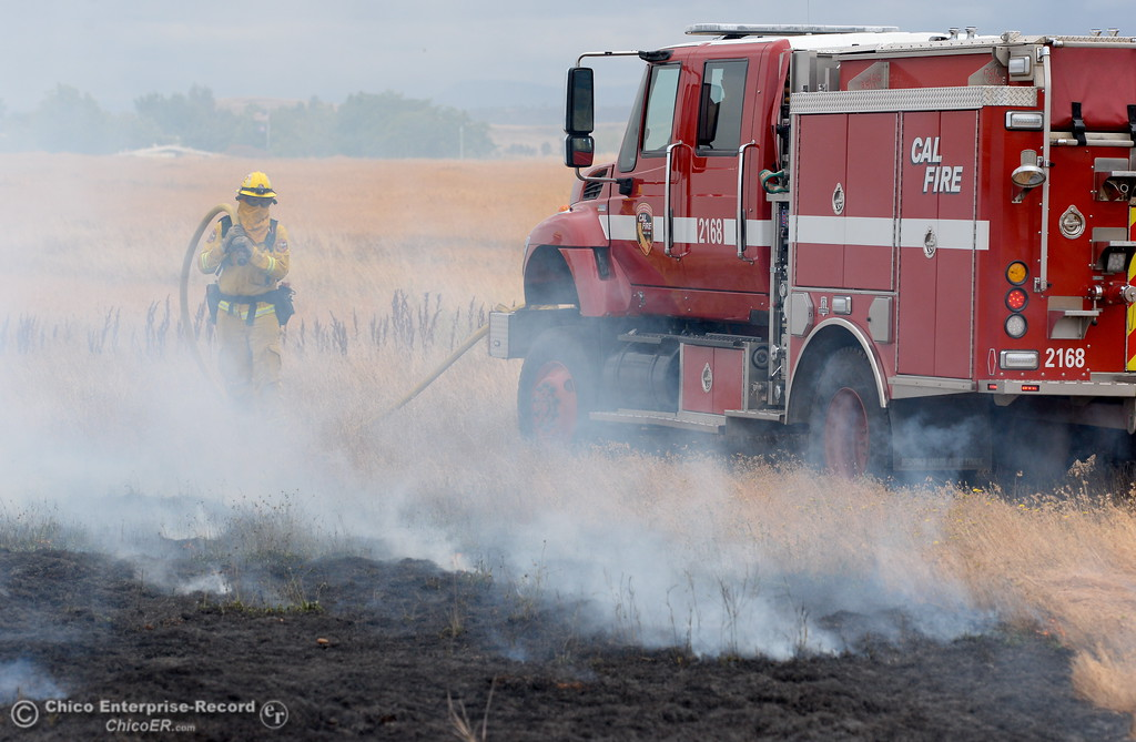 . CAL FIRE/Butte County Fire Elliot Hopkins walks along with a truck as CAL FIRE/Butte County Fire Department lite controlled burns near the Oroville Airport Monday June 12, 2017. The live burns are training for new firefighters and help firefighters study fire behavior in a controlled environment. (Bill Husa -- Enterprise-Record)