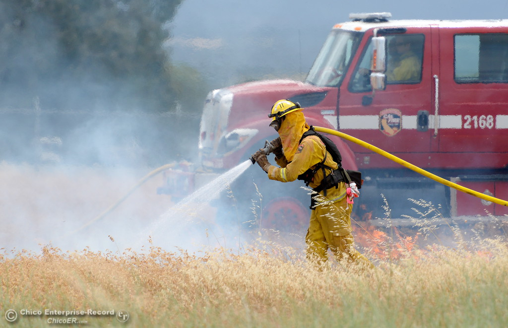 . CAL FIRE/Butte County Fire D.J. Patterson walks along side of a truck as CAL FIRE/Butte County Fire Department lite controlled burns near the Oroville Airport Monday June 12, 2017. The live burns are training for new firefighters and help firefighters study fire behavior in a controlled environment. (Bill Husa -- Enterprise-Record)