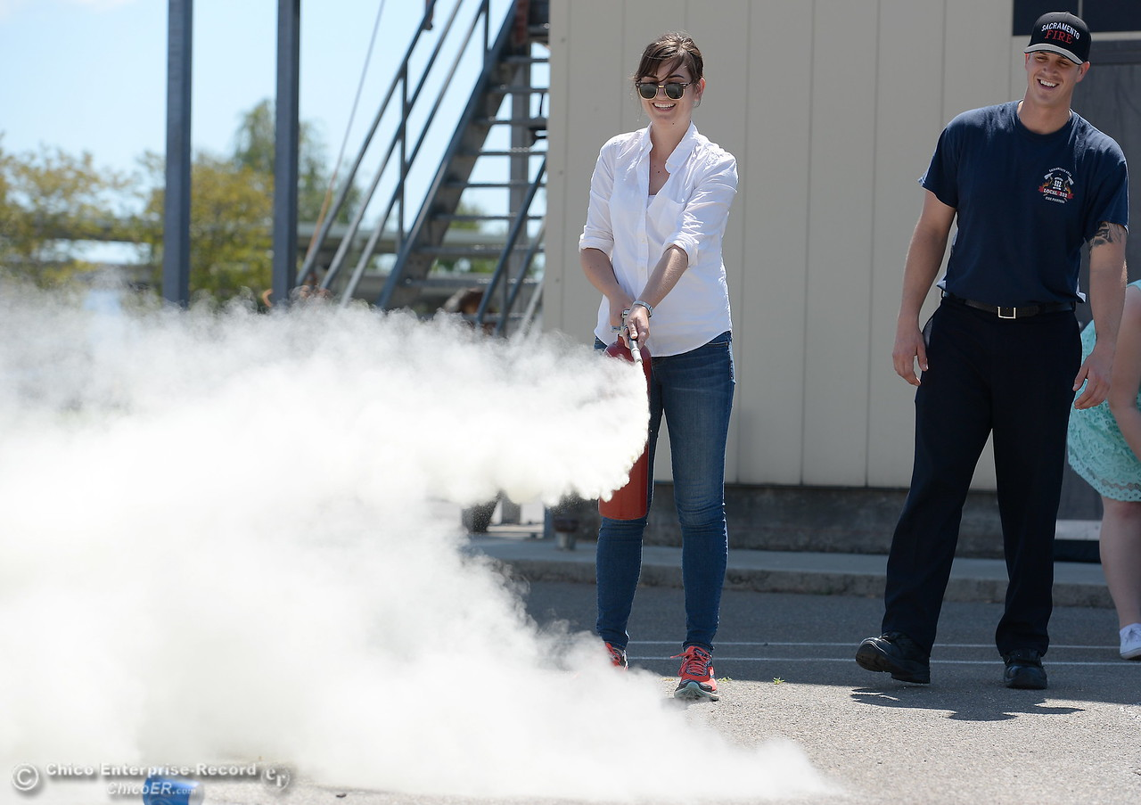 Chico ER Reporter Risa Johnson leans how to use a fire extinguisher as representatives from CAL FIRE, PG&E, Butte County Sheriff's Dept. teach fire safety to a group of media representatives during a fire safetly training held at the Butte College Training facility Monday, June 19, 2017. (Bill Husa -- Enterprise-Record)