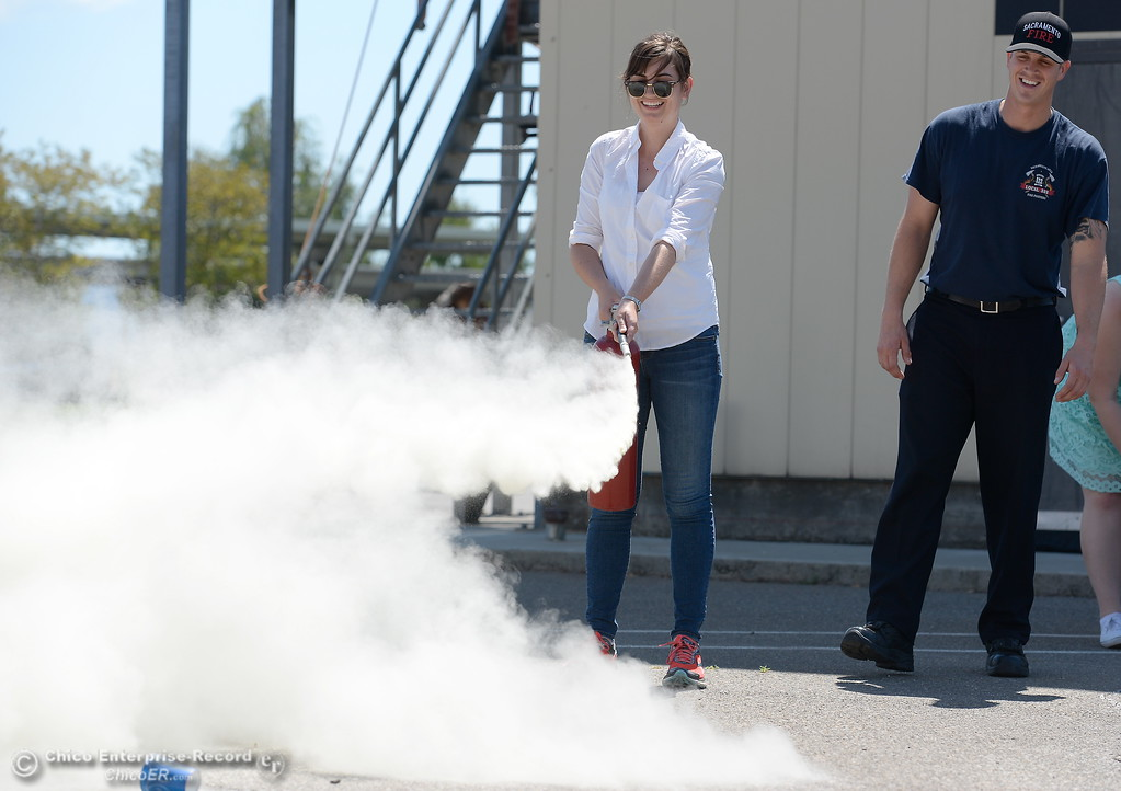 . Chico ER Reporter Risa Johnson leans how to use a fire extinguisher as representatives from CAL FIRE, PG&E, Butte County Sheriff\'s Dept. teach fire safety to a group of media representatives during a fire safetly training held at the Butte College Training facility Monday, June 19, 2017. (Bill Husa -- Enterprise-Record)