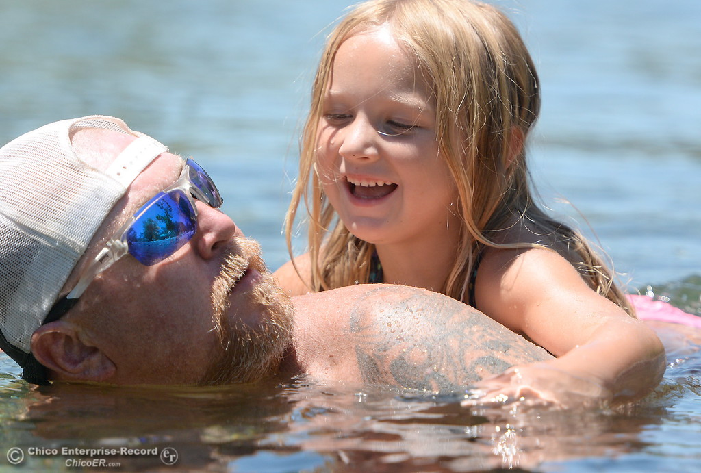 . Dad Joel Livingston gets a surprise attack from 6-year-old daughter Skylar Livingston while swimming in Butte Creek in Chico, Calif. Thurs. June 22, 2017.  (Bill Husa -- Enterprise-Record)