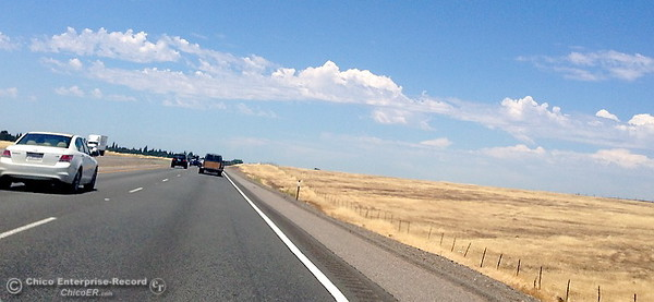 Vehicles make their way north on Hwy. 99 near Durham, Calif. through blistering heat as some patchy clouds are seen in the distance Monday June 19, 2017. (Risa Johnson/Chico Enterprise--Record)