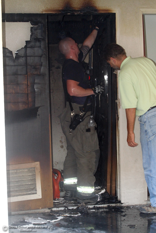 . Chico firefighter Tyler Sassen and City of Chico combination building inspector Rick Vagts assess the fire damage  in a water heater closet of an apartment that caught fire around 3:30 p.m. on  Citrus Avenue Monday June 19, 2017 in Chico, California. (Emily Bertolino -- Enterprise-Record)