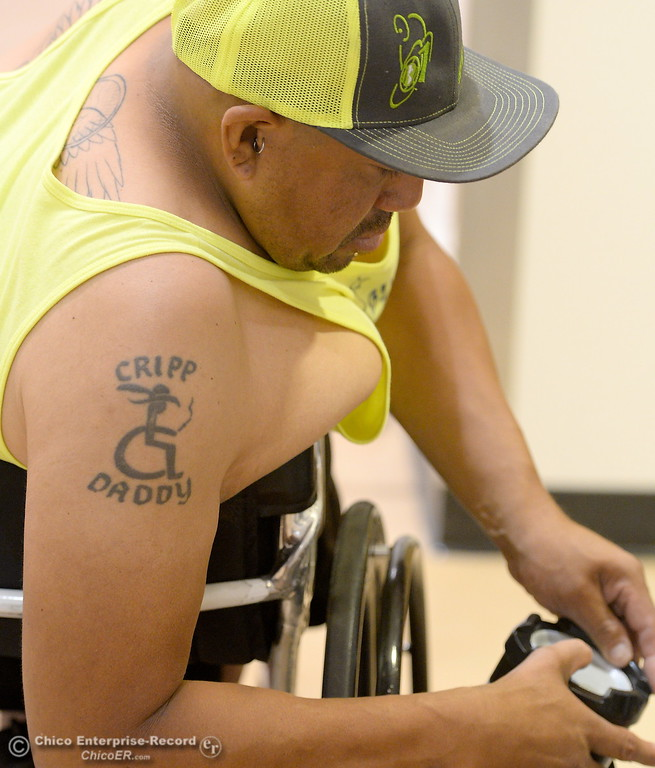 """. Tennis Instructor Anthonhy Lara of Chino, Calif. sports a \""""Cripp Daddy\"""" tattoo as he gets some music going during the Ability First Camp for kids with disabilities at CSUC Tuesday June 20, 2017. (Bill Husa -- Enterprise-Record)"""