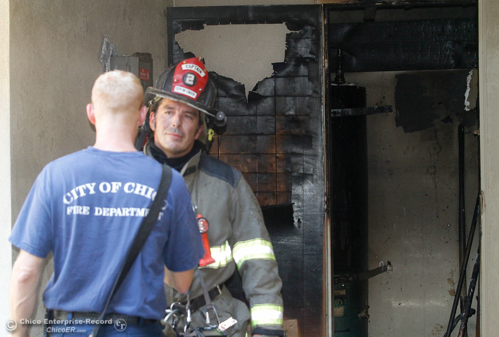 . Chico Fire Captain Carlos Munoz talks with engineer  Dominick Peloso after firefighters quickly put out an apartment building fire that started in the water heater closet on  Citrus Avenue Monday June 19, 2017 in Chico, California. (Emily Bertolino -- Enterprise-Record)
