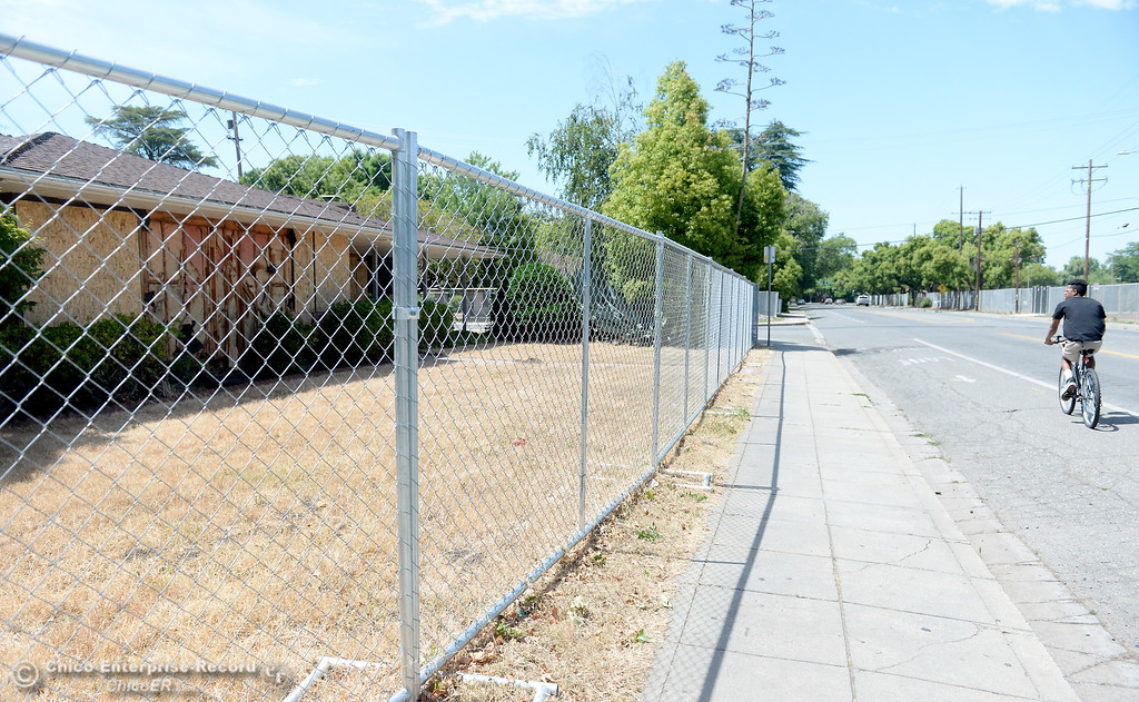 . A man on a bicycle rides past a home along Warner Street that is fenced off and scheduled for demolition as construction around Chico State University is underway in Chico, Calif. Wednesday May 30, 2018. (Bill Husa -- Enterprise-Record)