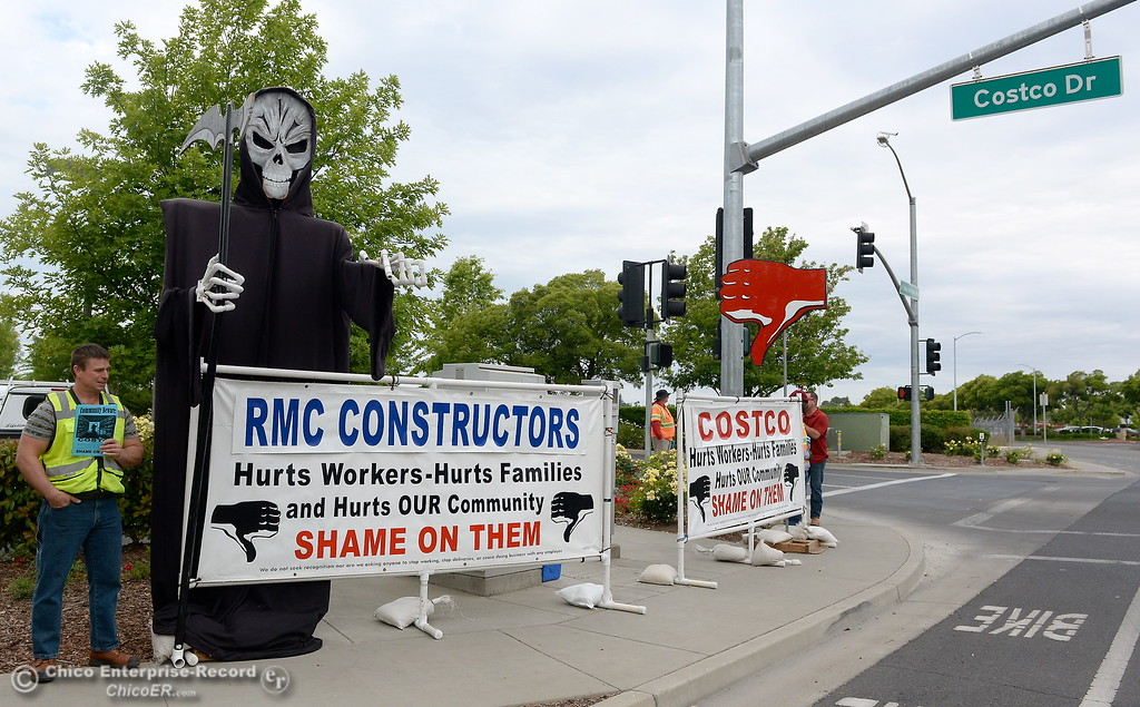 . People who refused to give their names stand beside a display along Martin Luther King Jr. Blvd in Chico Calif. handing out flyers stating that Costco and RMC Constructors are hurting workers, families and communities by not paying standard area wages or providing training and apprenticeships Wed. May 16, 2018. The flyer is marked with a Carpenters Local Union 701 label and encourages phone calls to voice outrage to CEO\'s of the companys.  (Bill Husa -- Enterprise-Record)