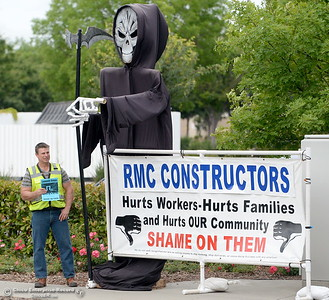 People who refused to give their names stand beside a display along Martin Luther King Jr. Blvd in Chico Calif. handing out flyers stating that Costco and RMC Constructors are hurting workers, families and communities by not paying standard area wages or providing training and apprenticeships Wed. May 16, 2018. The flyer is marked with a Carpenters Local Union 701 label and encourages phone calls to voice outrage to CEO's of the companys.  (Bill Husa -- Enterprise-Record)