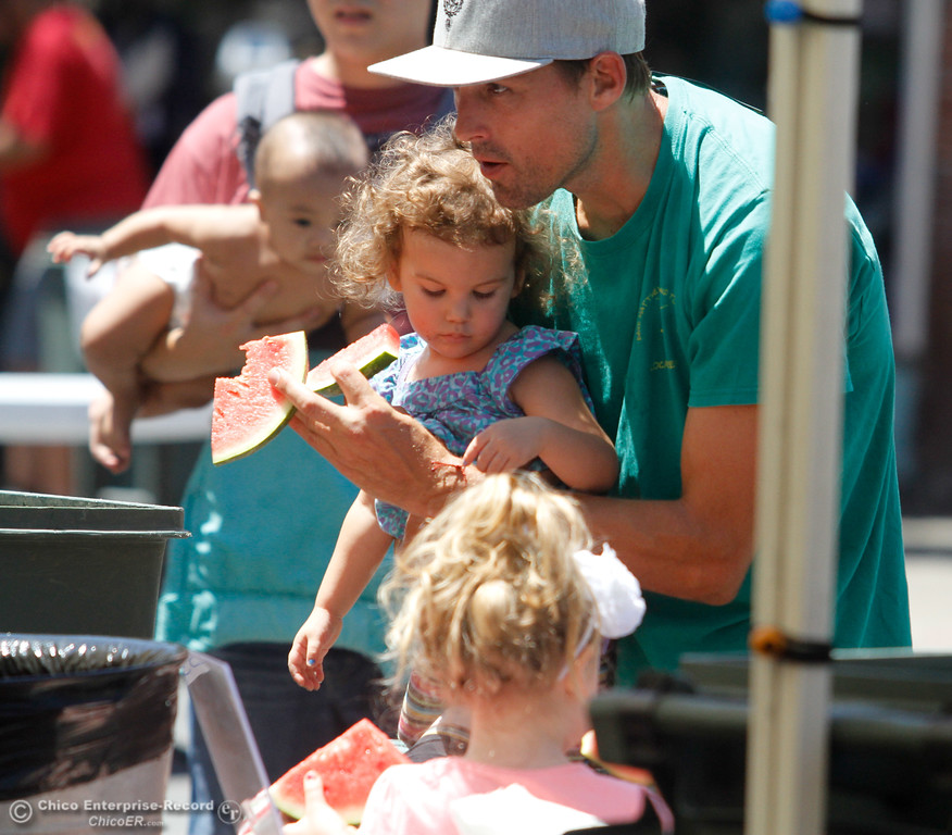 . A family grabs ice cold slices of watermelon during the annual Slice of Chico Saturday July 15, 2017 in Chico, California.  (Emily Bertolino -- Enterprise-Record)