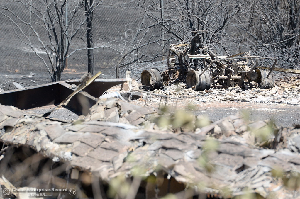 . The charred remains of a vehicle is seen beside a structure that was also lost at Bardolino Lane and Viewcrest Drive after the Wall Fire near Oroville, Calif. Mon. July 10, 2017. (Bill Husa -- Enterprise-Record)