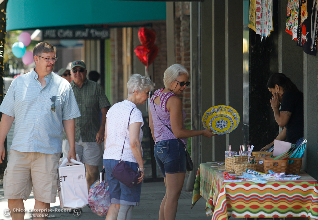 . People browse merchandise in front of Zucchini & Vine during the annual Slice of Chico Saturday July 15, 2017 in Chico, California.  (Emily Bertolino -- Enterprise-Record)