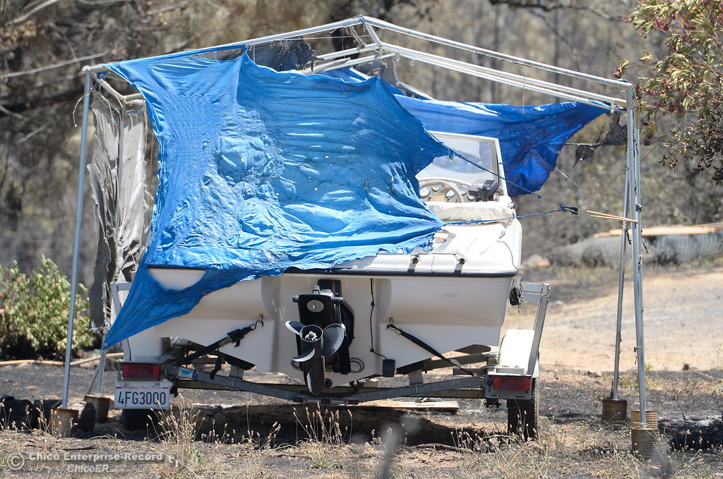 . A melted tarp hangs partially over a boat after the Wall Fire near Oroville, Calif. Mon. July 10, 2017. (Bill Husa -- Enterprise-Record)