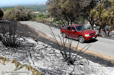 A vehicle makes it's way past charred brush after the Wall Fire near Oroville, Calif. Mon. July 10, 2017. (Bill Husa -- Enterprise-Record)