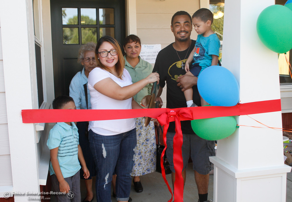 . The Bruhns family cuts down the celebratory ribbon and receives the keys to their new home during the Habitat for Humanity of Butte County Home Dedication Ceremony Saturday July 15, 2017 in Chico, California.  (Emily Bertolino -- Enterprise-Record)