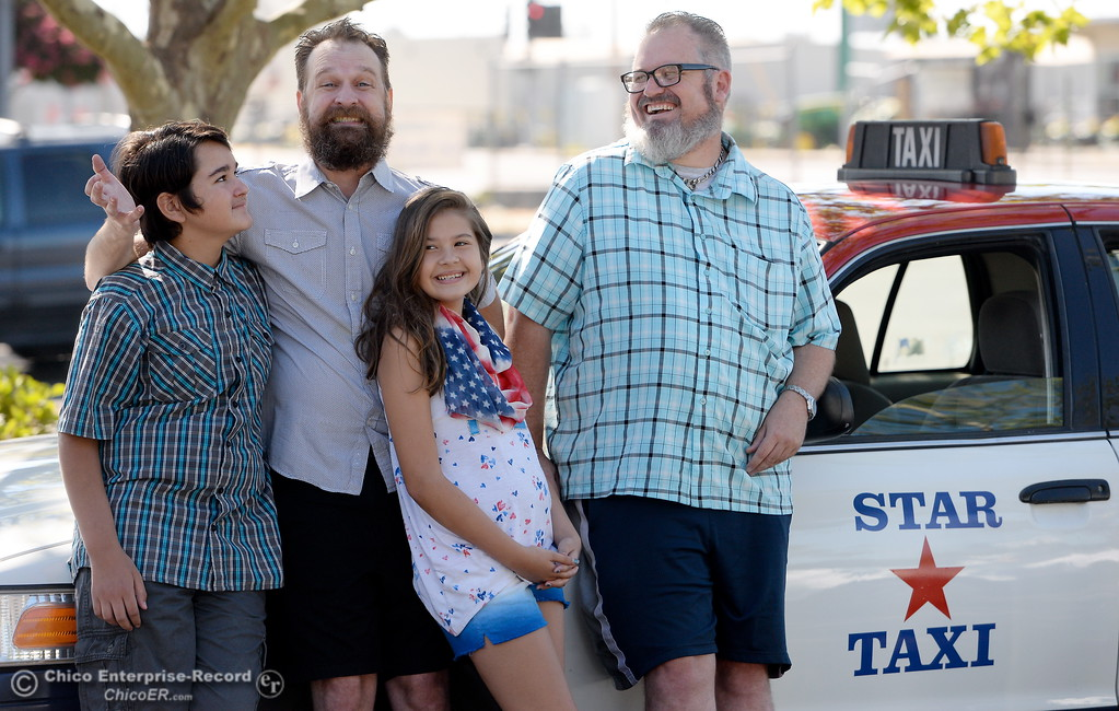 . Taxi driver Erik Schmidt and his children Judith, 13 and Luna 11, at left smile beside Taxi driver Shawn Heater and a cab company car in Chico, Calif. Monday 7-17-2017. (Bill Husa -- Enterprise-Record)