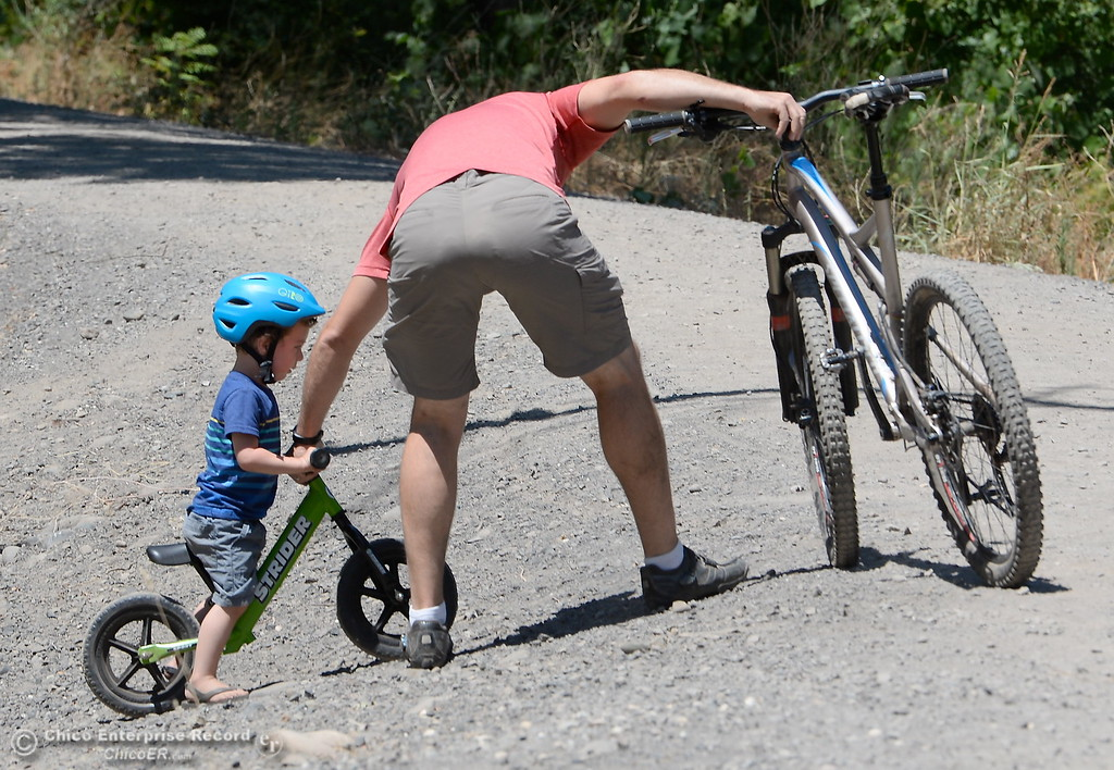 . Dad Jeff Blake of Chico helps out 2-year-old Jason as they enjoy a ride near the Five Mile Recreation area in Upper Bidwell Park in Chico, Calif. Wed. July 19, 2017. (Bill Husa -- Enterprise-Record)