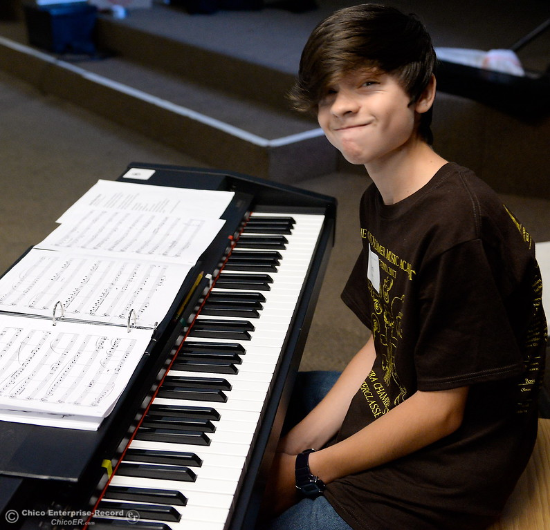 . Evan Herrera looks up with a smile as Seven of the 34 pianists who will perform at the upcoming Monster Piano Concert practice under the direction of Dr. Allan Miller and Marci Pittman at the Bidwell Presbyterian Church in Chico, Calif. Thurs. July 20, 2017. The pianists include Autumn Riley, Sarah Grace-Arington, Natalie Potkin, Daisy Ferris, Sarah Katris-Tyler, Hunter Smith and Evan Herrera. The concert is Saturday, July 22, 3:00 p.m. at Bidwell Presbyterian Church in Chico, Calif. (Bill Husa -- Enterprise-Record)