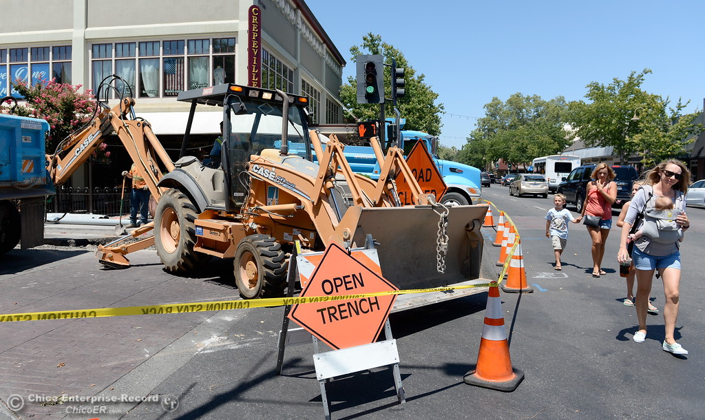 . Pedestrians walk by as PG&E works near the corner of Main St. and W. Third Street as PG&E is upgrading the underground electric system in downtown Chico after there was an underground cable failure and fire in June. Construction on this is expected through July 21. Tuesday July 18, 2017. (Bill Husa -- Enterprise-Record)