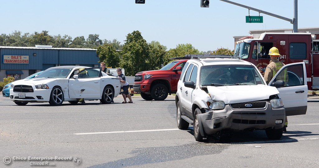 . Firefighters check on drivers following a two vehicle collision between a Dodge Charge and Ford Escape at the Skyway and Bruce Road intersection in Chico, Calif. Wed. July 19, 2017. One driver appeared slightly injured and traffic was blocked on Bruce Road for a time. (Bill Husa -- Enterprise-Record)